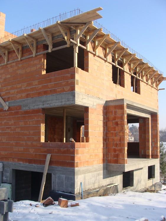 Budynek w stanie surowym otwartym ściany z czerwonego pustaka ceramicznego, żelebtowe wieńce obwodowe stropów, drewniany szalunek pod wysunięty wspornikowo okap dachu.