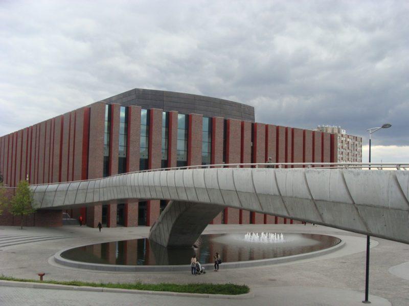 NOSPR Katowice. Panorama obiektu od strony Katowickiego Spodka. Ceglane elewacje i żelbetowa kładka łacząca NOSPR z centrum konferencyjnym.