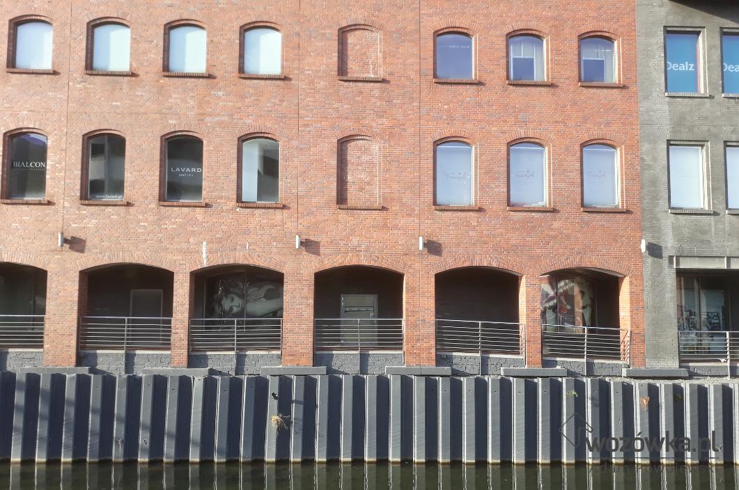 Widok ceglanej elewacji galerii handlowej nad miejskim kanałem. Łukowe nadproża okien i podcieni murowane na rolkę stojącą . Węgarki okien wycofane madają historyczny charakter współczesnej elewacji.